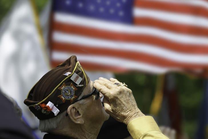 Senior veteran saluting at flag.