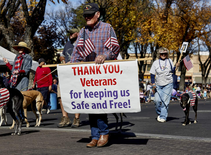 elderly man at a parade with a sign thanking veterans