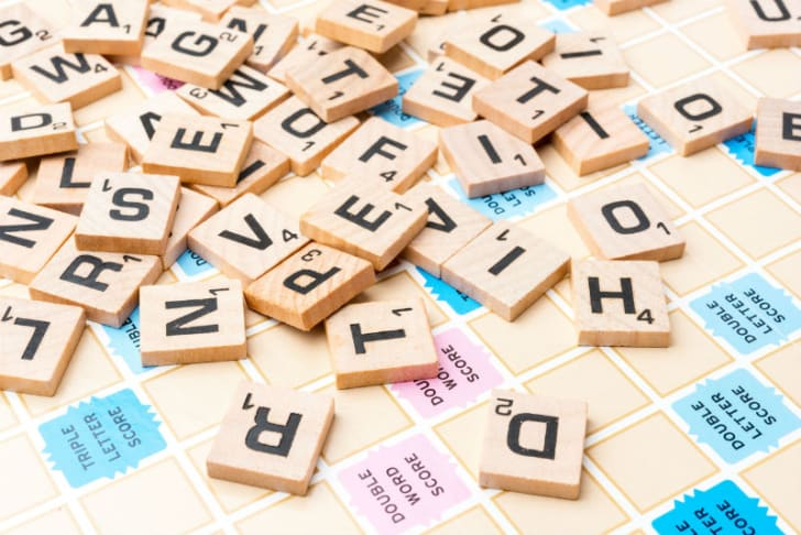 Scrabble tiles are scattered across the board