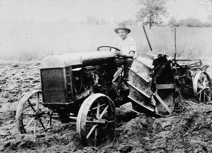 A man sits in the driver seat of the first Ford tractor, circa 1920.