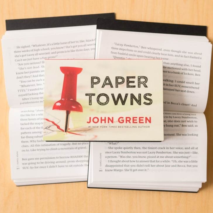 A copy of the Penguin Mini version of 'Paper Towns' resting on two open copies of the book