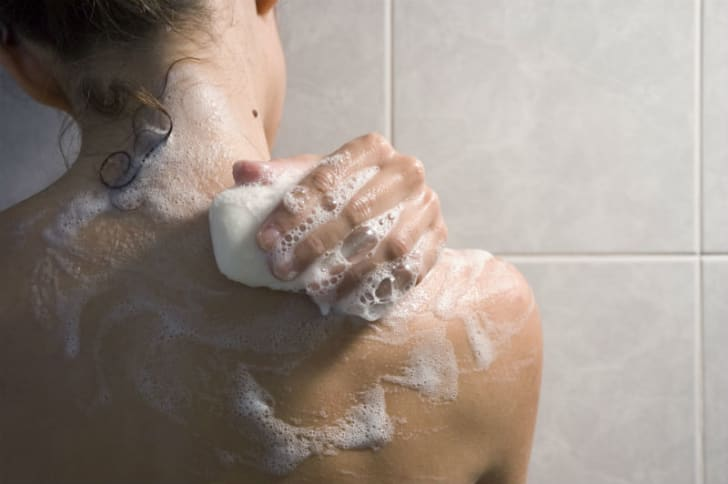 A woman uses a bar of soap in the shower
