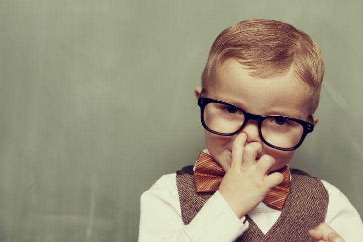 A child picks his nose