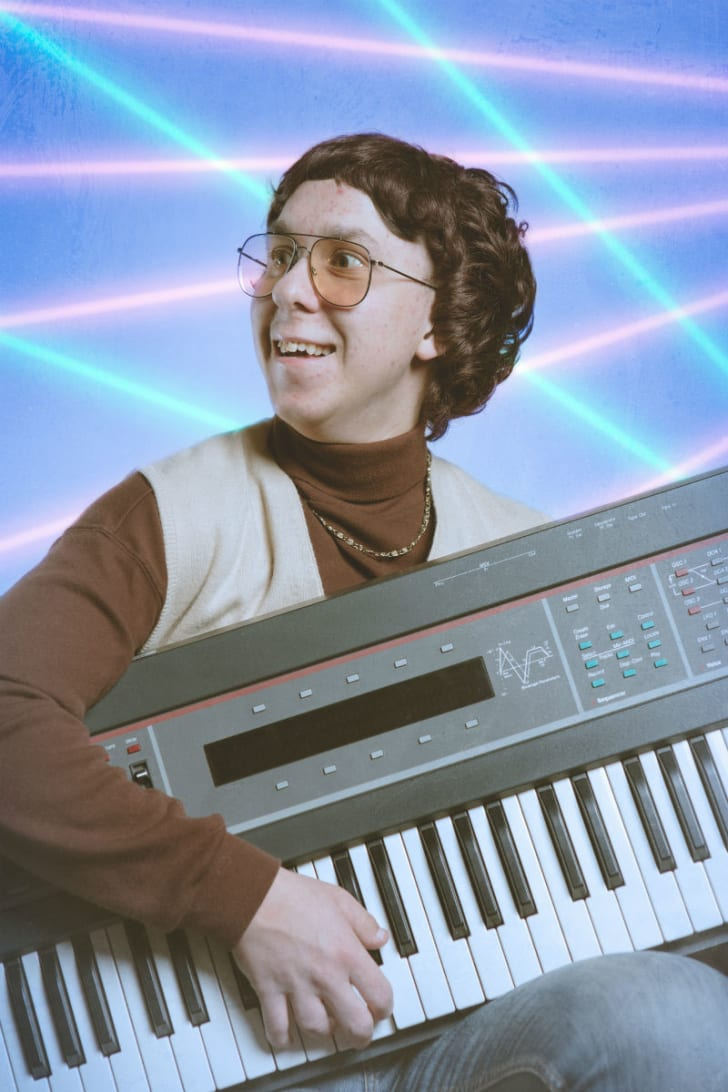 A student poses for a school photo with an electronic keyboard