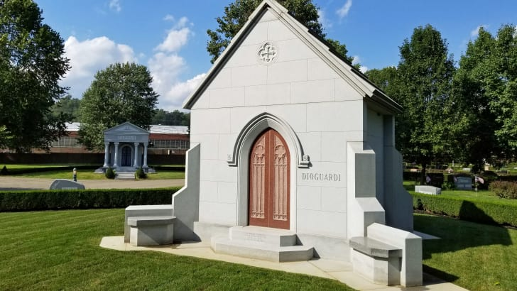 A mausoleum in a graveyard on a sunny day