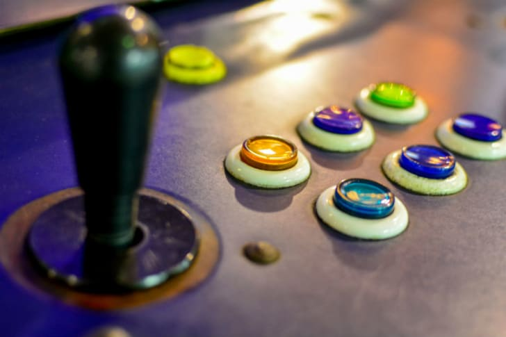An arcade game joystick sits next to buttons