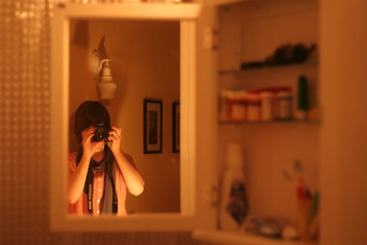 A woman takes a photo of herself in a medicine cabinet mirror