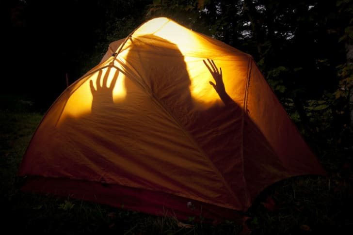 A person's shadow is visible in a camping tent