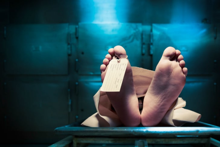 A toe tag is seen on a corpse in a morgue