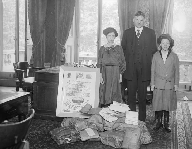 In 1918, Herbert Hoover was the director of the United States Food Administration, and was closely associated with relief efforts Europe. Here, he is standing with his wife and daughter by a poster giving thanks to America for its help in providing food.