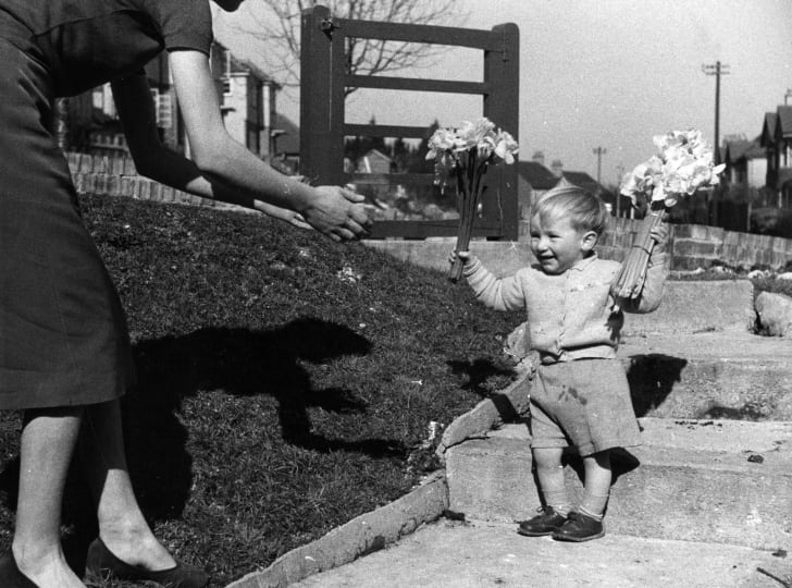 A little boy gives his mother some flowers