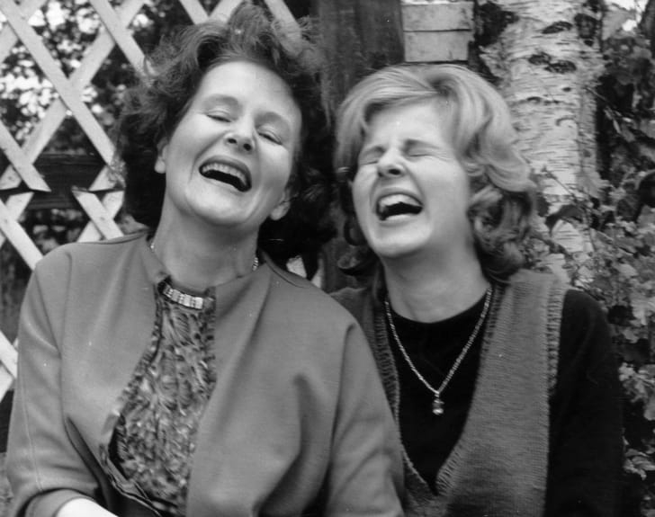 Two women laughing together.