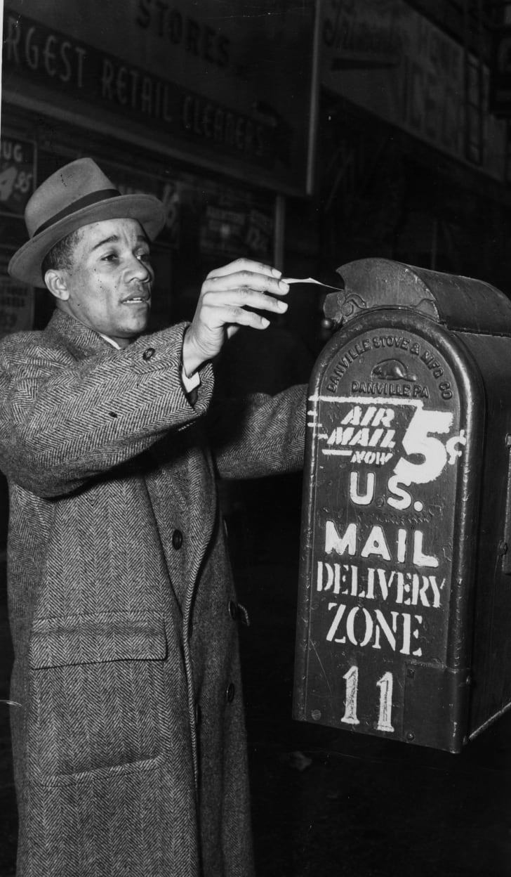 A man mailing a letter in 1960s New York.