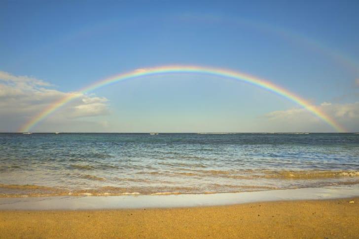 A rainbow appears over the ocean