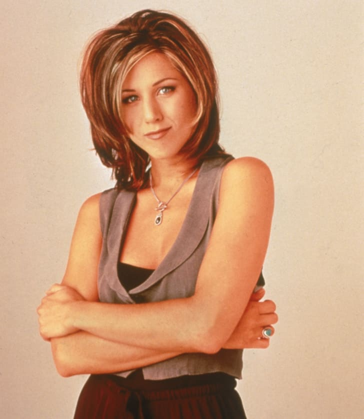 A promotional image of Jennifer Aniston with her arms crossed, 1995