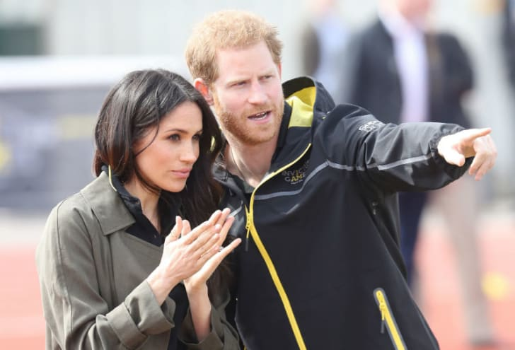 Prince Harry and Meghan Markle stand on the sidelines