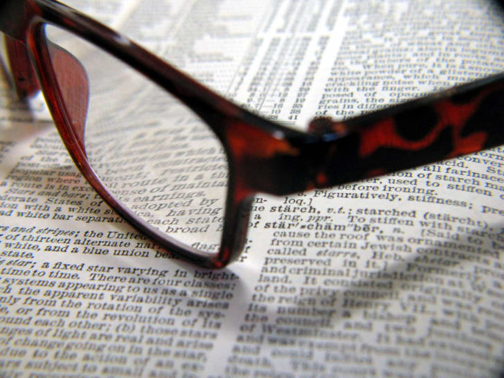 A pair of reading glasses on a dictionary.