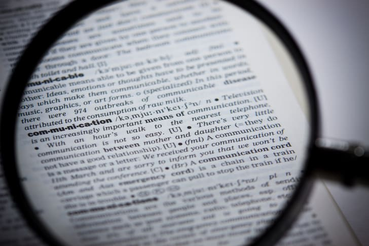 Magnifying glass looking at a dictionary.
