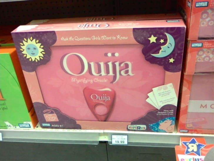 Pink Ouija board on toy store shelf.
