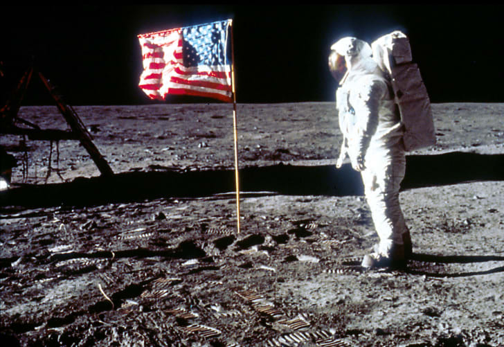 Buzz Aldrin poses next to an American flag on the surface of the Moon.