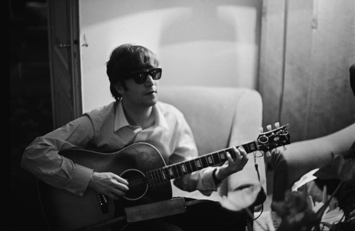 John Lennon (1940 - 1980) of the Beatles plays the guitar in a hotel room in Paris, 16th January 1964