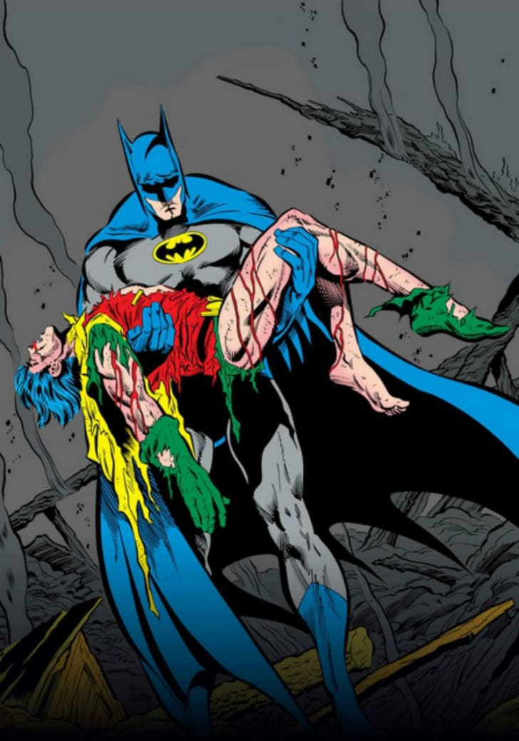 Batman holds an injured Robin in a DC Comics illustration by Jim Aparo