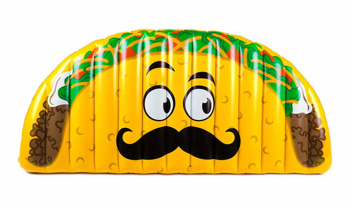 A pool float shaped like a taco with a face on it.