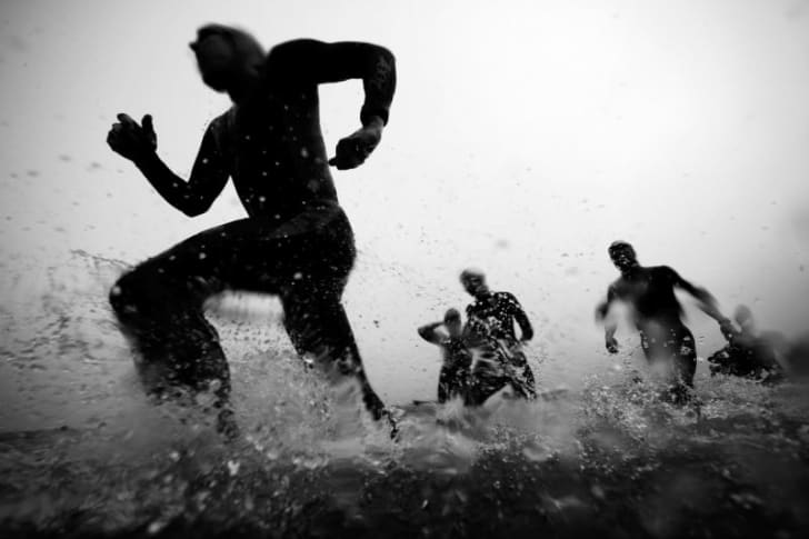 Swimmers run across the water near Alcatraz Island