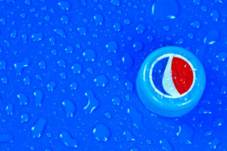 A Pepsi bottlecap is pictured against a blue background