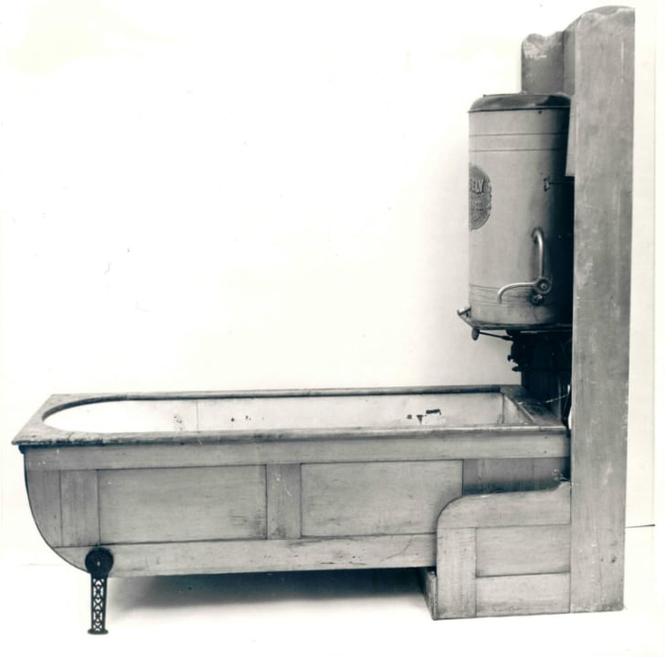 A folding bathtub is depicted with the tub unfolded