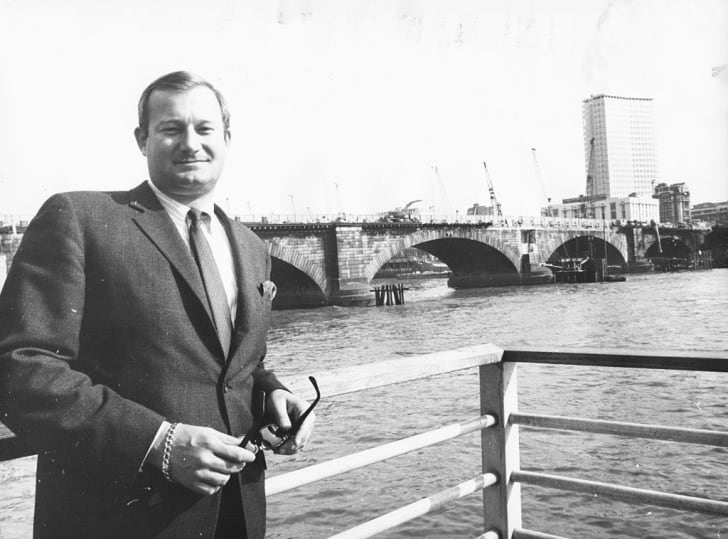 Robert McCaulloch standing in front of London Bridge as it is dismantled in 1968