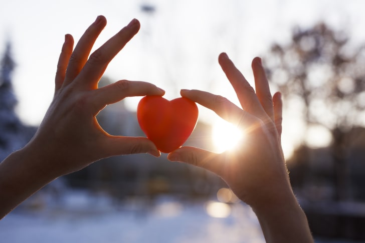 Hands holding a cut-out heart in the air.