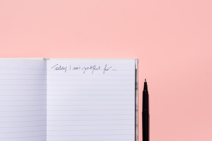 Gratitude journal on a pink background.