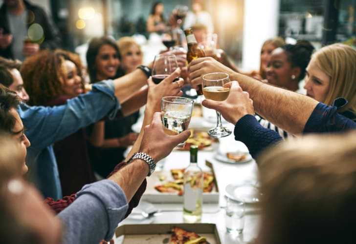 Friends toasting around a table.