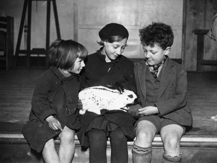 Three children hold a rabbit, 1935.
