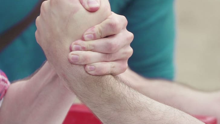 Two hands appear in close-up during an arm wrestling contest