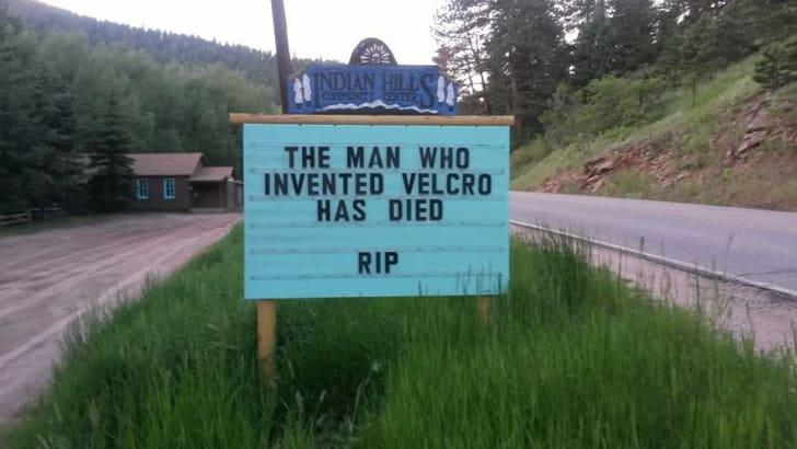 "A sign reads ""The man who invented Velcro has died. RIP."""