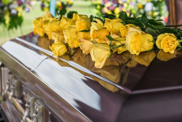 Yellow flowers sit on top of a coffin