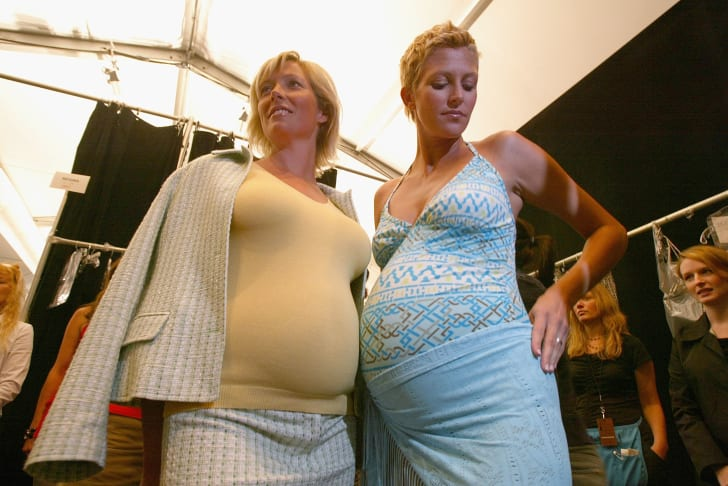 Pregnant models prepare backstage for the Liz Lange Couture Show during NYFW in September 2004.