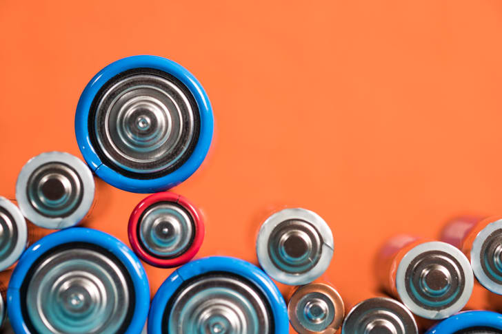 Assorted batteries on an orange background.