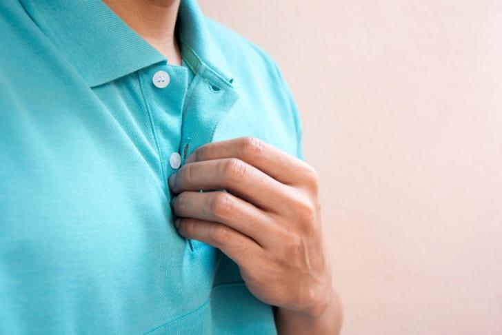 A man buttons his shirt