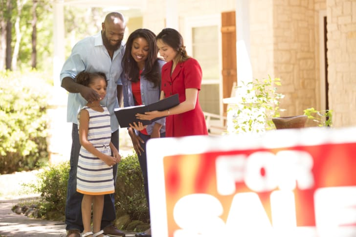 A realtor and family looking at a new home to purchase