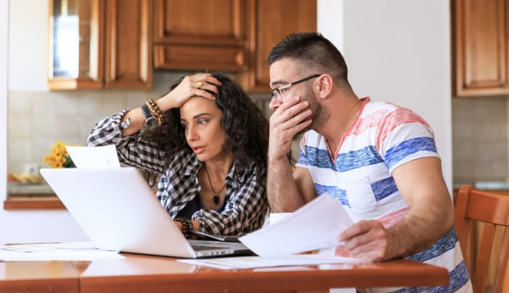 A stressed-out looking couple reviewing files near a laptop