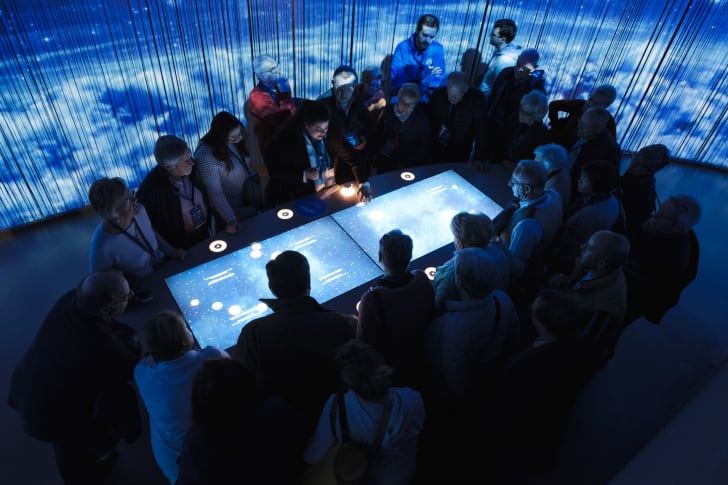 Visitors look down at an interactive museum table in a dark room