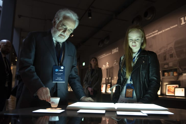 A man and a young woman examine a museum installation