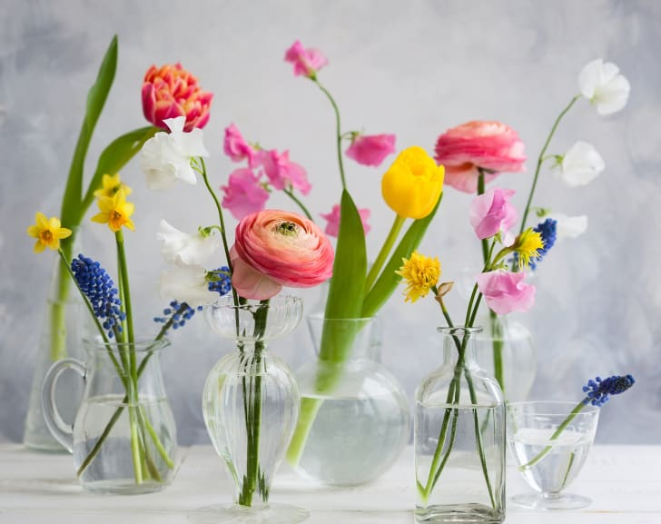 Bright, beautiful flowers in several clear vases.