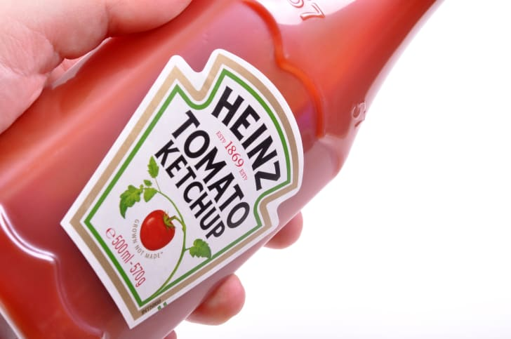 A ketchup bottle being held in someone's hand.