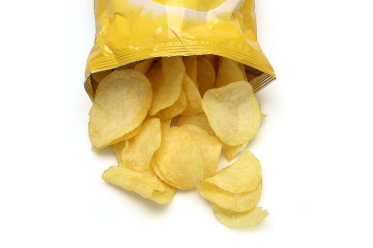 An open bag of potato chips with the chips spilling out.
