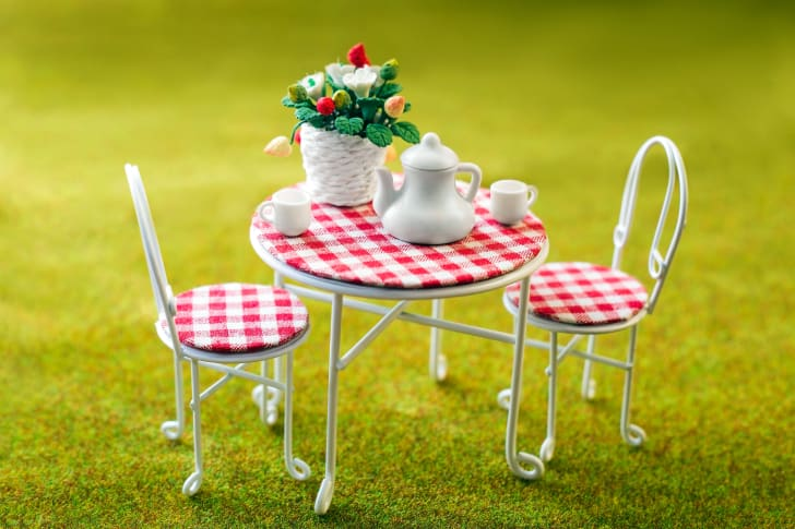 miniature garden furniture with tea service and flowers