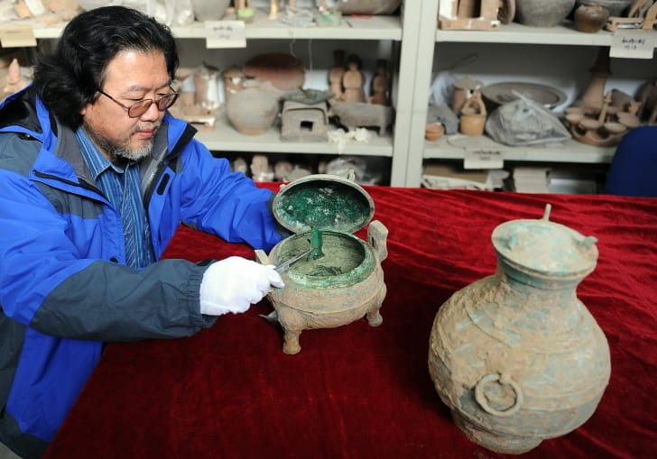 An archaeologist holds a bronze vessel where soup was found inside